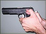 This is the classic Thumb-over-Thumb grip as espoused by Jeff Cooper, with the stronghand thumb riding the safety lock of the 1911 pistol.