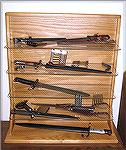 "Here is my new bayonet display case.  Solid oak, glass shelves, with a plexiglass cover to keep out dust (not shown).  See the next image, ""Bayonet Display II,"" for descriptions of the content."